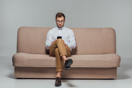 stylish man in eyeglasses sitting on couch and using smarttphone isolated on grey