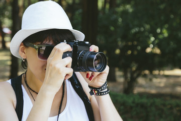 Girl with white hat taking photo with vintage camera beautifulbeautiful girlbrunettecameracaucasianfadedfedoraforestgirlhathipsterlenslifestyleoldold cameraphotophotographerportraitretroretro camerasu