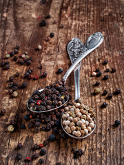 Black and white fragrant pepper peas in spoons on a wooden background