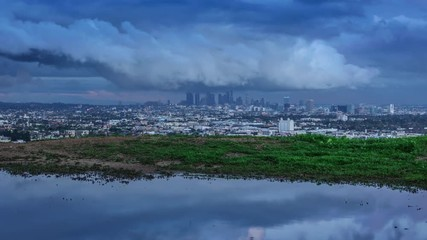 Klistermärke - Zoom in on Los Angeles cityscape skyline under storm clouds reflecting in puddle from sunset to night 4K UHD timelapse