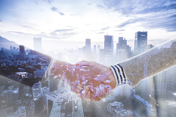 Close up image of business partners handshake over office desk during meeting or negotiation.