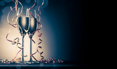 Two glasses with sparkling champagne and decorative ribbons