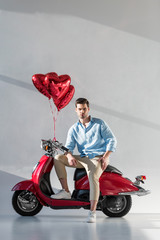 young man with heart shaped balloons sitting on red scooter