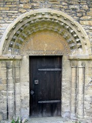 Old wooden front door to the old church-built stone
