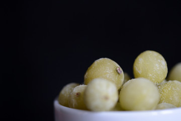 Frozen gooseberries on a dark background close up