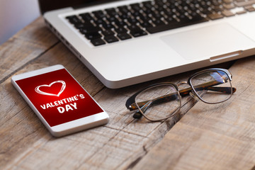 Mobile phone with Valentine's day card in the screen, with a laptop and eye glasses over a wooden table.