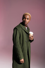 Stylish young african american man holding paper cup and looking away isolated on violet background