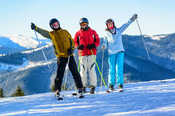 Three happy skiers having fun on winter ski slope