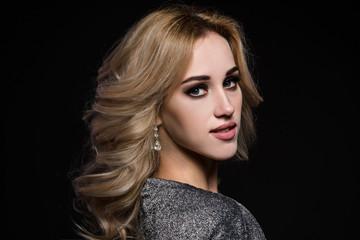Studio beauty portrait of gorgeous blonde woman on black background