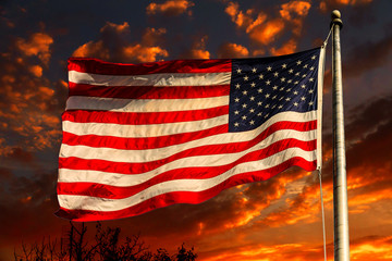 American flag in front of bright sky with white clouds