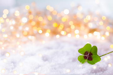 New Year Background  -  Four-leafed clover in snow landscape with bokeh lights