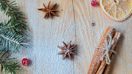 Powdered spices for mulled wine or Christmas bakery orange, anise, cinnamon,  fresh red viburnum berries on wooden background. Decorated with Christmas tree branch. Flat lay, copy space, top view