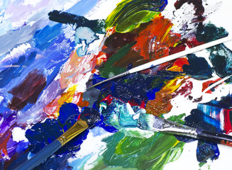Mixing of multi-colored paints with brushes on the art palette