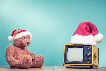 Teddy Bear toy watching retro TV in Santa hat front mint green background. Holidays congratulation in mass media concept. Vintage old style filtered photo