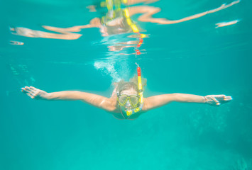 Young woman in mask is snorkeling in the tropical water.