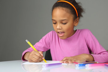 the girl draws a yellow pencil on white paper.