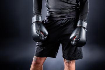 cropped shot of boxer in black gloves on black