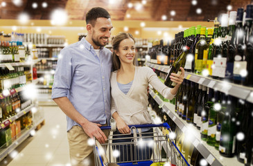 couple with wine and shopping cart at liquor store