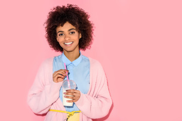 portrait of smiling african american woman with glass of milk on pink wall background