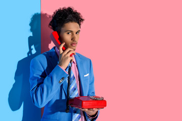 portrait of stylish african american man talking on retro telephone against pink and blue wall