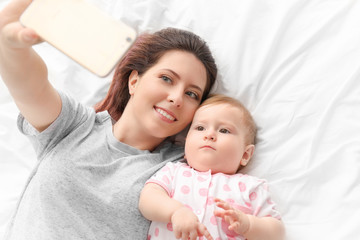 Young mother taking selfie with her cute baby on bed