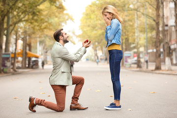 Young man with engagement ring making proposal to his beloved girlfriend outdoors