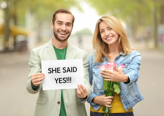 Young man holding paper with text SHE SAID YES and his happy beloved showing ring on engagement day outdoors