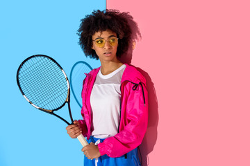 Young bright african american girl with tennis racket on pink and blue background