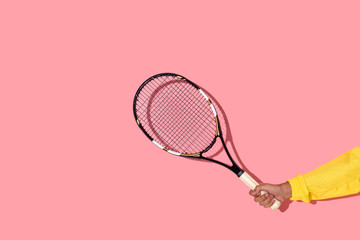 Widok z bliska męskiej ręki trzymającej rakietę tenisową na różowym tle - 185478681