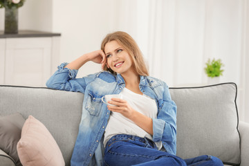 Beautiful woman drinking coffee while resting on sofa at home