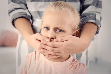 Woman covering little girl's mouth indoors. Child abuse concept