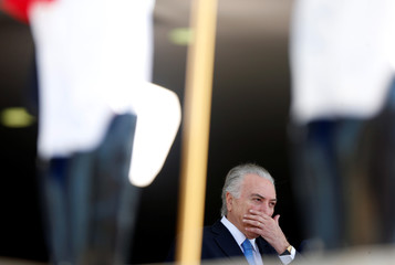 Brazil's President Michel Temer gestures as he stands behind honour guard before welcoming his counterparts during Mercosur trade bloc annual summit in Brasilia