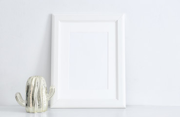 Empty frame and decorative cactus statuette on table near white wall