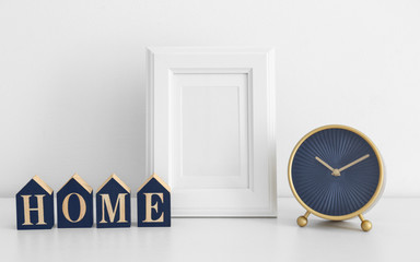 "Empty frame, vintage clock and wooden blocks with word ""Home"" on table near white wall"