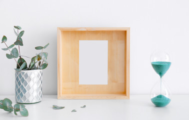 Empty wooden frame, hourglass and eucalyptus on table near white wall