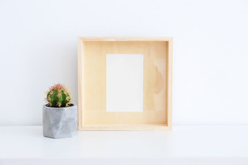 Empty wooden frame and cactus on table near white wall