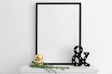 Empty black frame and decor on table near white wall