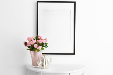 Empty frame, pink roses and decorative cactus statuette on table near white wall