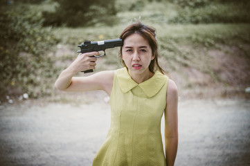 Stressed woman with holding gun on hand point to her head.She is saddened by the disappointment in love. concept of breaken heart, heartbroken, lovelorn, Suicide.