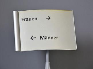 Schild in einem Amt. Frauen rechts und Männer links.