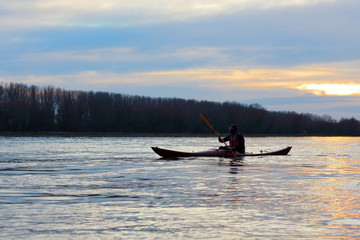 Sillouette of man kayaking on Danube river at sunset. Winter kayaking. Sports and recreation.