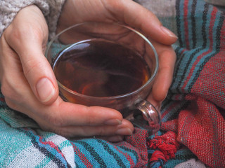Transparent Cup of hot tea on a blanket. Toning.