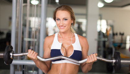 Young blonde woman workout with olympic bar in gym