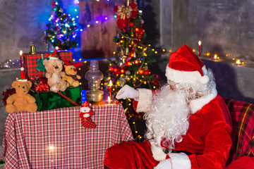 Santa claus at home,Sit on chair think about plan for sent gift box for give children
