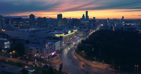 Fotobehang - Aerial view night city traffic and dark urban skyline beautiful sunset 4K UHD