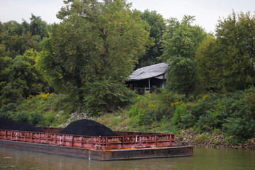 A run down barn sits next to a barge filled with coal on the banks of the Ohio River in Corydon