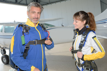 Male and female sky divers preparing their harnesses