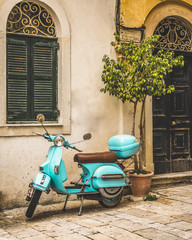 Foto auf Acrylglas Scooter Corfu, Greece- December 21, 2017: Narrow streets and alleys in Corfu town Greece.Architecture in the old town of Corfu is heavily influenced my the Venetian architecture.Blue Vespa outside a building.