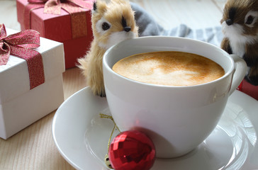 Two Cute squirrels are playing near coffee cup with background christmas 's gift.Christmas theme.
