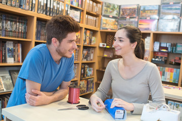 2 teens packing social game gift in game store